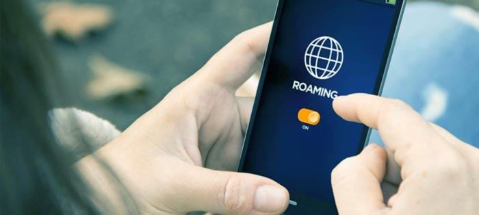 Mão segurando celular, ligando Roaming Internacional para empresa