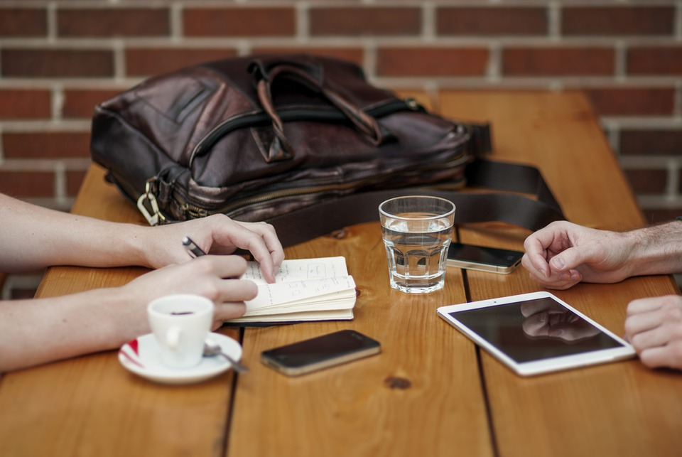 Reunião Help Consult, mesa com celulares e tablet, copo dágua e café